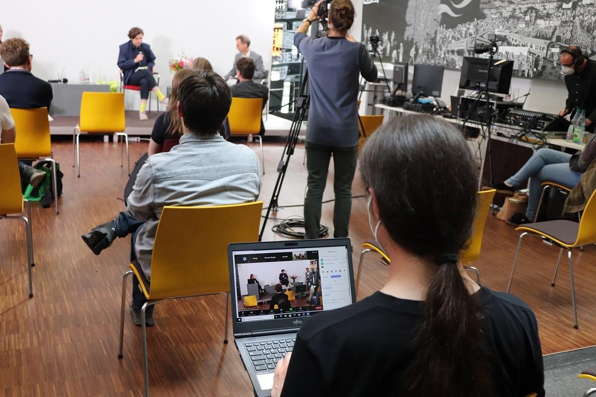 Publikum im realen und im Zoomraum. Foto: Kathrin Schwarz